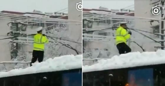 중국 안후이성에 내린 폭설로 도심 전기 케이블이 무너졌다. 중국 경찰이 버스 지붕에 올라 무너진 케이블을 정리하고 있다. [웨이보 캡처]