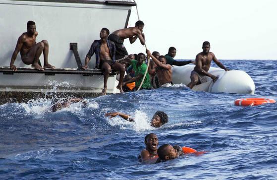지난 6일(현지시간) 리비아 해안에서 해안 경비대의 구명선에 올라타는 난민들. 구조되지 못한 5명은 사망했다. (Lisa Hoffmann/Sea-Watch via AP) <저작권자(c) 연합뉴스, 무단 전재-재배포 금지>