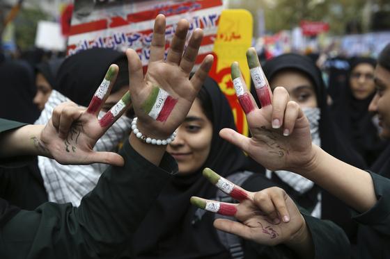 지난해 11월 '테헤란 주재 미대사관 검거 사건' 30주년을 맞아 반미 시위를 벌이고 있는 이란 여학생들. 이란 국기 색깔을 덧칠한 손에 '미국에 죽음을'이라는 페르시아어가 적혀 있다. [AP=연합뉴스]