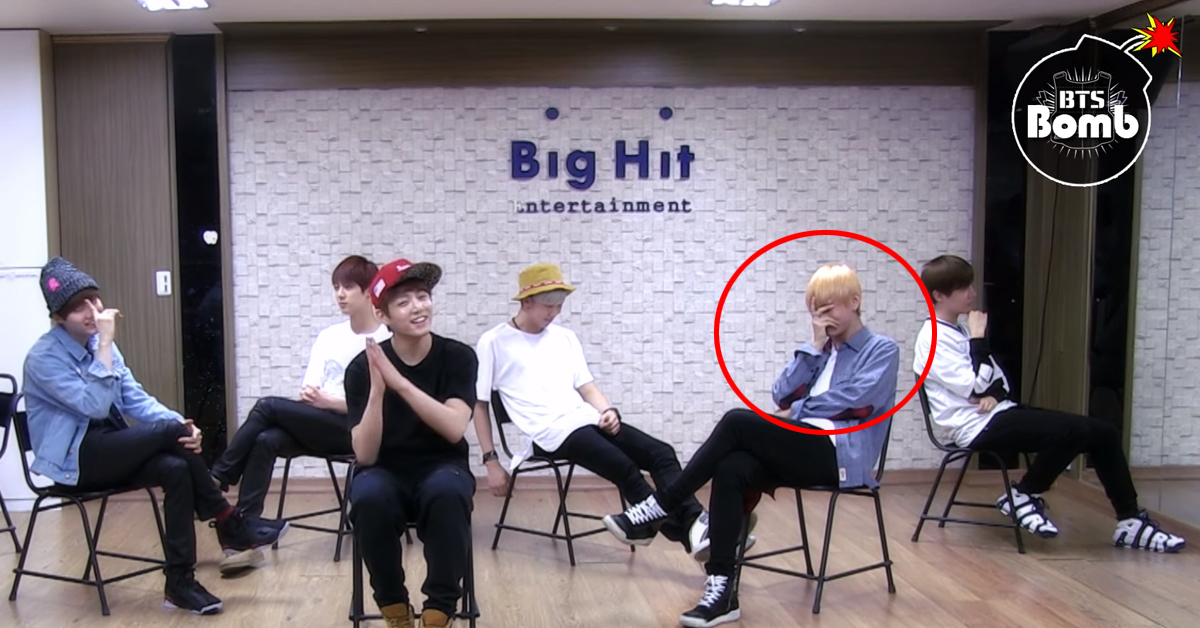 V hides his face behind his hands.