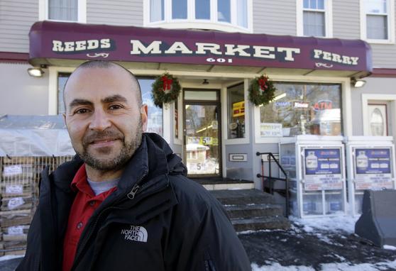 미국 파워볼 1등 판매점 '리즈페리마켓' 주인인 삼 사파가 자신의 상점앞에서 웃고 있다. 삼 사파는 파워볼 1등을 판매 함으로서 7만5000달러의 보너스를 받게됐다. [AP=연합뉴스]