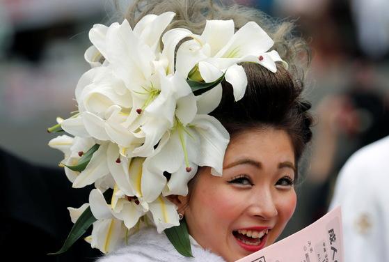 머리에 꽃장식한 한 여성이 8일 일본 도쿄의 한 공원에서 열린 성인식에 참석하며 활짝 웃고 있다. [로이터=연합뉴스]
