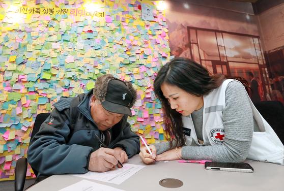 남북 고위급 당국회담이 열린 9일 서울 남산 대한적십자사에서 김영식 할아버지(왼쪽)가 이산가족 상봉 신청서를 작성하고 있다. 이날 정부는 북측에 설을 계기로 이산가족 상봉 행사 개최를 제안했다. [임현동 기자]