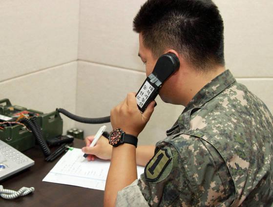 군 과계자가 지난 2103년 9월 단절됐던 서해지구 군 통신선 복원을 위해 시험통화를 하고 있다. [사진 연합뉴스]