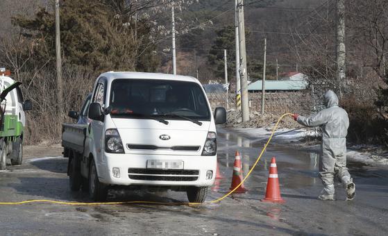 지난 4일 경기도 포천시 영북면 한 산란계 농장에서 AI(조류인플루엔자)가 확인되자 방역 관계자가 농장 부근을 출입하는 차량을 소독하고 있다. 임현동 기자