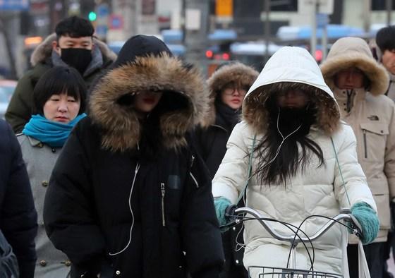 서울 아침 최저기온이 영하 13도까지 떨어진 지난 11일 아침 출근길 시민들이 두꺼운 외투를 입고 서울 광화문 횡단 보도를 건너고 있다. 김상선 기자