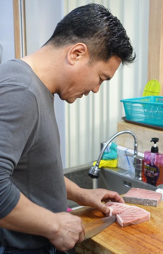 '작은수산시장'의 초덮밥 메뉴를 만든 주인의 동생 채성태씨가 참치 뱃살 초덮밥을 만들려고 회를 뜨고 있다.