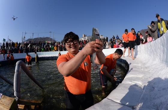지난 6일 개막한 강원도 화천군 산천어축제장을 찾은 관광객이 맨손으로 산천어를 잡은 모습. 축제장에선 얼음낚시와 얼음썰매 등 체험프로그램도 즐길 수 있다. [사진 화천군]