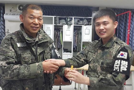 전역하는 병사에게 손수 만든 나무 도장과 반지를 선물하고 있는 김만수 원사(왼쪽). [사진 육군]