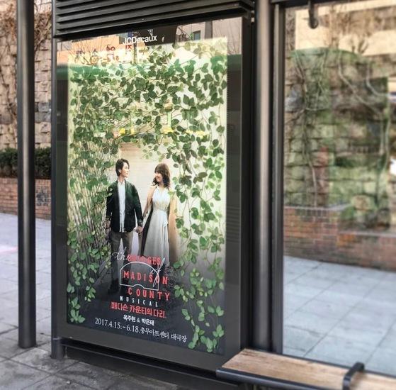 뮤지컬 '매디슨 카운티의 다리' 버스정류장 광고. 초록색 잎으로 주위를 채워 환상적인 느낌을 연출했다. [사진 슬로우 파마씨]