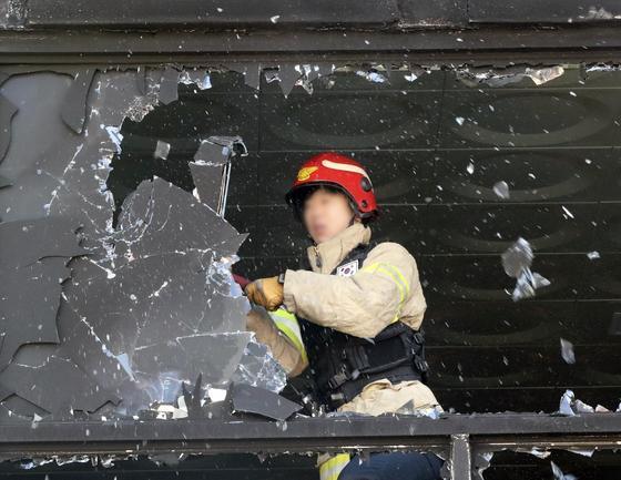 제천소방서 구조대원이 지난해 12월 26일 화재 참사가 발생한 제천 스포츠센터 건물 2~3층의 통유리 제거 작업을 하고 있다. [연합뉴스]