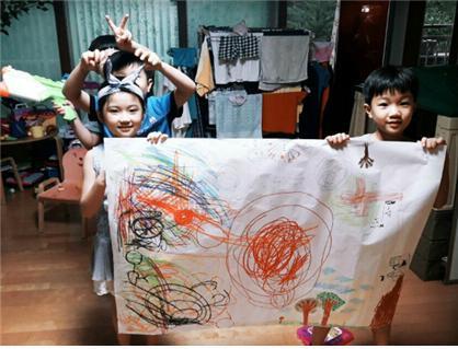 서경대 재학생이 서경지식나누미 프로그램 참여해 지역 주민 자녀에게 미술수업을 하고 있다. 수업 결과물을 들고 포즈를 취한 주민 자녀들.