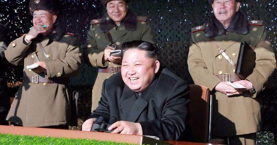 북한군 방사포 부대가 청와대 모형을 향해 로켓 공격을 하고 있다. 훈련장을 찾은 김정은은 관람대에서 이 를 지켜보며 웃었다.  [사진제공=노동신문]