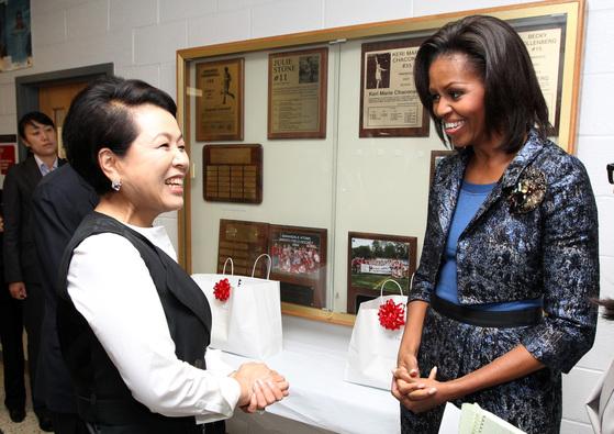 지난 2011년 10월 14일 김윤옥 여사와 미셸 오바마와 공립학교 방문  이명박 대통령의 부인 김윤옥 여사가 13일(현지시간) 버지니아 애난데일 고등학교에서 미셸 오바마 여사와 이야기를 나누고 있다.