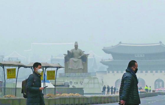 이번 달 들어 서울 등 수도권에서는 미세먼지 비상저감 조치가 세 차레나 발령됐으나. 실효성 논란이 제기됐다. 마스크를 쓴 시민들이 미세먼지가 가득 찬 서울 광화문 광장을 지나고 있다. [중앙포토]