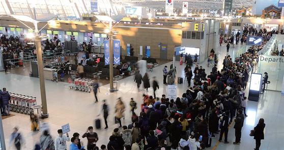 지난해 설 명절 연휴를 앞둔 인천공항 출국장에 여행객들이 줄지어 서 있다.