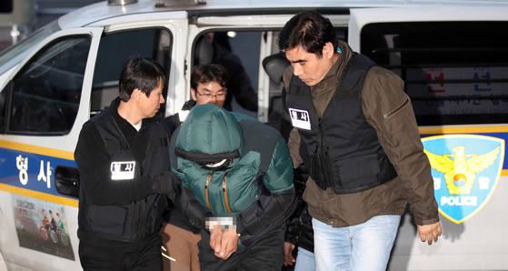 술에 취해 여관에 불을 질러 5명이 숨지는 참사를 일으킨 종로 여관 방화범 유모씨가 20일 오후 서울 종로경찰서 유치장으로 이송되고 있다. [연합뉴스]