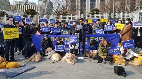 동물권단체 '케어' 회원들이 21일 오후 서울 종로구 정부서울청사 앞에서 체고 40cm 이상의 개 입마개 의무화에 반대하며 퍼포먼스를 하고 있다. [동물권단체 케어 제공=연합뉴스]