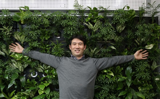 하츠 김성식 대표가 식물을 활용한 공기 정화시스템인 '버티걸 에어가든' 앞에서 포즈를 취했다. 벽면에 식물을 길러 공기 중 유해 물질을 정화하고, 습도를 조절해 실내 환경을 쾌적하게 만든다. [김상선 기자]