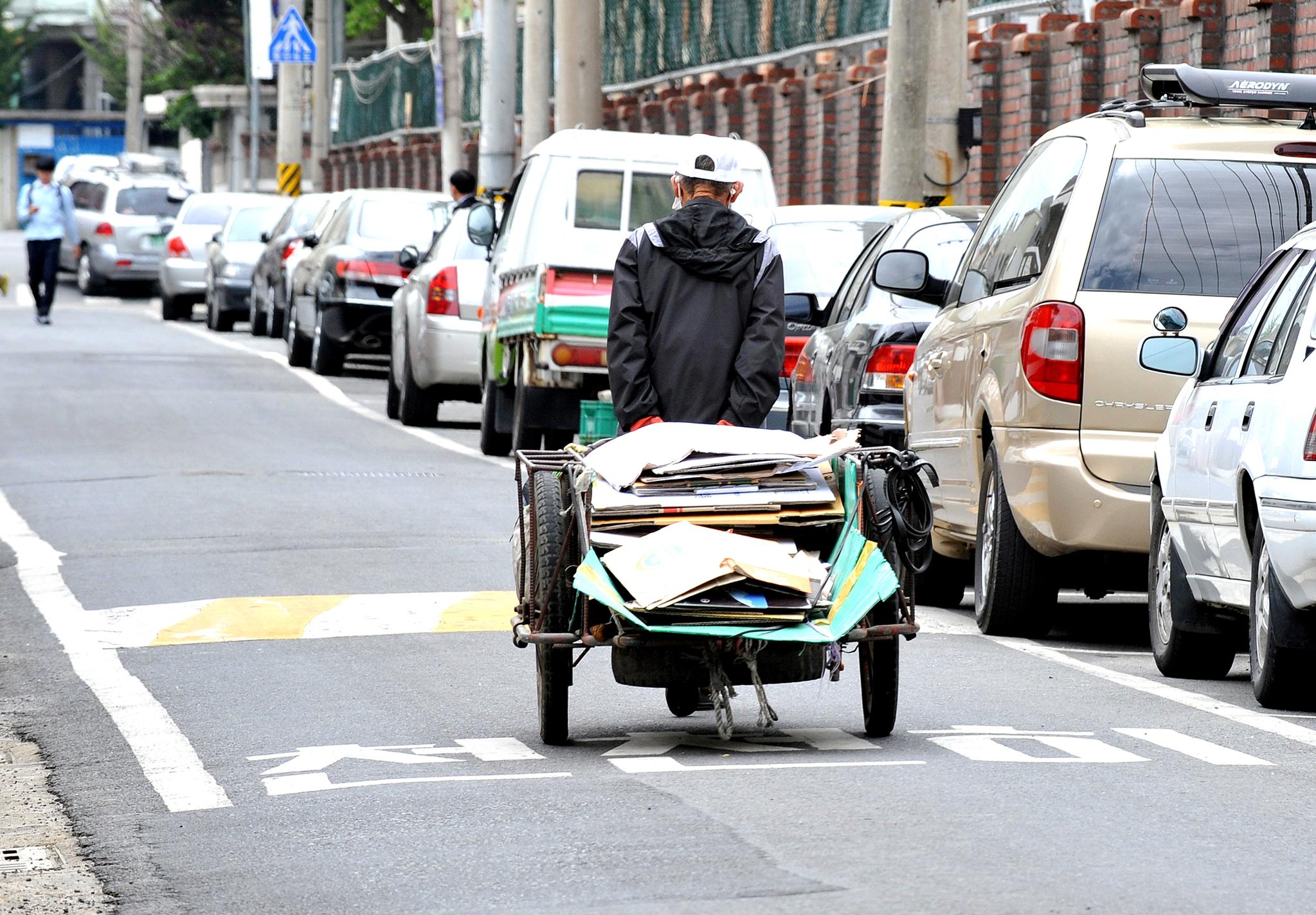 한 노인이 재활용품을 실은 리어카를 끌고 가는 뒷모습. 기준중위소득 70% 이하 노인은 기초연금을 받아 소득으로 삼는다. [중앙포토]