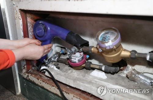전국에 최강 한파가 몰아닥친 지난 11일 오후 서울 용산구 이촌동의 한 아파트에서 주민이 동파로 교체된 수도 계량기를 헤어드라이어로 녹이고 있다. [연합뉴스]