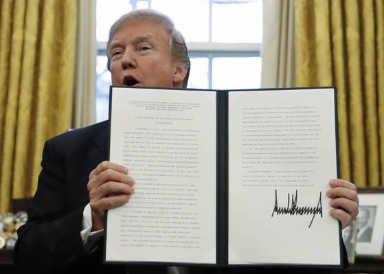 도널드 트럼프 미국 대통령이 23일 백악관에서 한국산 세탁기 등에 세이프가드(긴급수입제한조치)를 발동하는 행정조치에 서명한 뒤 이를 들어 보이고 있다.[AP=연합뉴스]