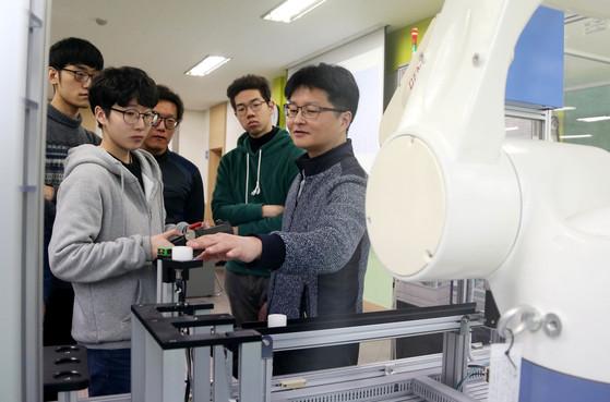 대한상공회의소 인천인력개발원 교육생들이 지난 22일 무인 공장에서 활용될 협동로봇을 제어하는 실습을 하고 있다. [사진 대한상공회의소]