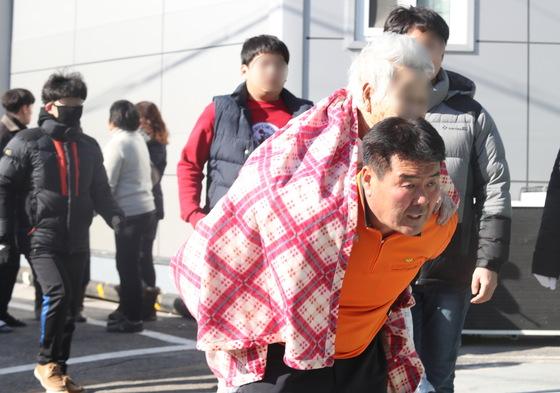 26일 오전 7시 30분 경남 밀양시 가곡동 세종병원에서 불이나 소방대원이 환자를 업고 긴급히 대피시키고 있다. [연합뉴스]