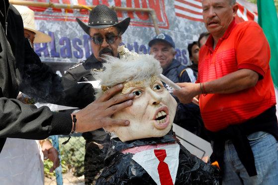 멕시코의 활동가들이 지난 20일 수도 멕시코시티의 미국 대사관 앞에서 도널드 트럼프 미국 대통령의 취임 1주년을 맞아 그를 닮은 종이 인형을 전시한 채 항의 시위를 벌이고 있다. [로이터=연합뉴스]