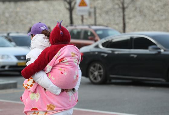 중부지방을 중심으로 영하권의 추위가 이어진 28일 서울 종로구 인사동 인근에서 엄마가 아이를 업고 횡단보도를 건너고 있다. [연합뉴스]