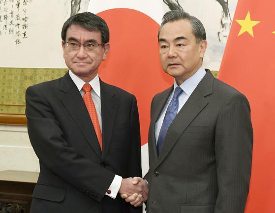 고노 다로(河野太郞) 일본 외무상(왼쪽)과 왕이(王毅) 중국 외교부장이 28일 중국 베이징(北京)에서 회담을 열기 전에 알수를 나누고 있다. 두 외교장관은 회담 모두발언을 통해 양국 관계 개선의 필요성을 강조하며 덕담을 나눴다. [베이징 교도=연합뉴스]