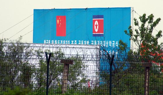 2011년 6월 북한과 중국이 합작하기로 한 황금평 개발 착공식. 현수막 앞으로 북중 국경 철조망이 보인다. [연합뉴스]