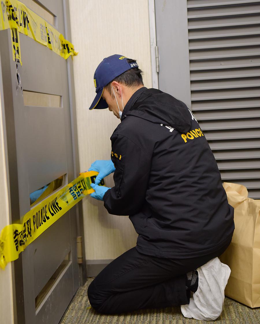 경찰이 자살 현장을 보존하기 위해 출입금지 스티커를 붙이고 있다. [중앙포토]