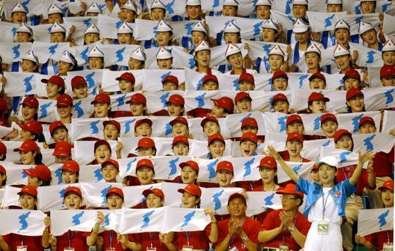 남북은 평창동계올림픽 참가 관련 실무회담에서 230여명 규모의 북한 응원단 파견에 합의했다. 사진은 2003년 대구하계유니버시아드대회에서 한반도기를 흔드며 응원전을 펼치는 북한 응원단.중앙포토