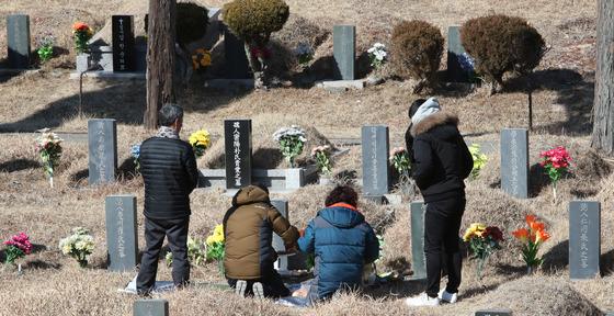 전국적으로 한파가 몰아친 지난 4일 설날을 십여일 앞두고 부산 금정구 영락공원을 찾은 한 가족이 미리 성묘를 하고 있다. [중앙포토]