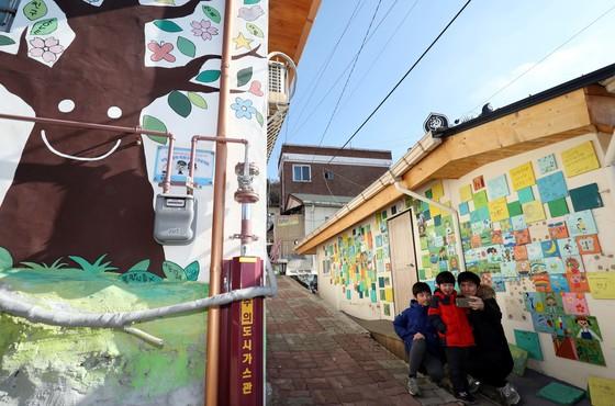 청주시 상당구 수암골에서 한 방문객이 벽화 앞에서 사진을 찍고 있다. [프리랜서 김성태]