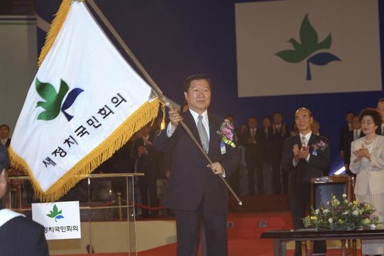 1995년 9월 5일 새정치국민회의 창당대회에서 당기를 흔들고 있는 김대중 당시 국민회의 총재. [중앙포토]