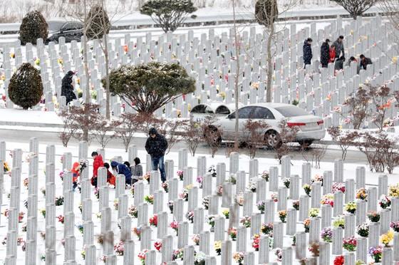 민족 최대 명절 설 연휴를 사흘 앞둔 12일 국립대전현충원을 찾은 참배객들이 눈이 소복히 쌓인 묘비에서 성묘하고 있다. 김성태 프리랜서