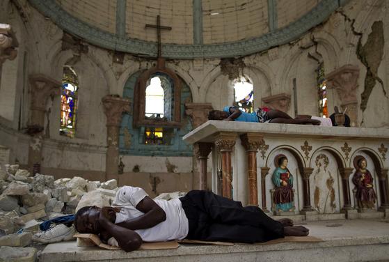 2010년 1월 대지진으로 삶의 터전을 잃은 아이티 이재민들이 수도 포르토프랭스의 부서진 산타 아나 교회에서 잠을 청하고 있다. [AP=연합뉴스]
