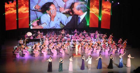 지난 11일 오후 서울 국립중앙극장 해오름극장에서 열린 북한 삼지연 관현악단 공연에서 가수 서현이 함께 '우리의 소원은 통일'이라는 제목의 노래를 부르고 있다. [사진 연합뉴스]