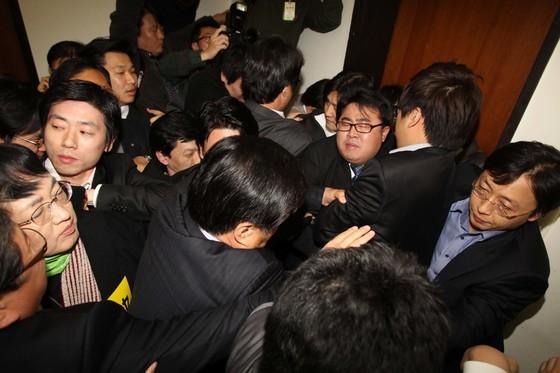 7일 저녁 한나라당 국토해양위 소속 의원들이 회의실을 점거하자 야당 의원및 보좌관들이 문열어라하면 몸싸움을 벌이고 있다.