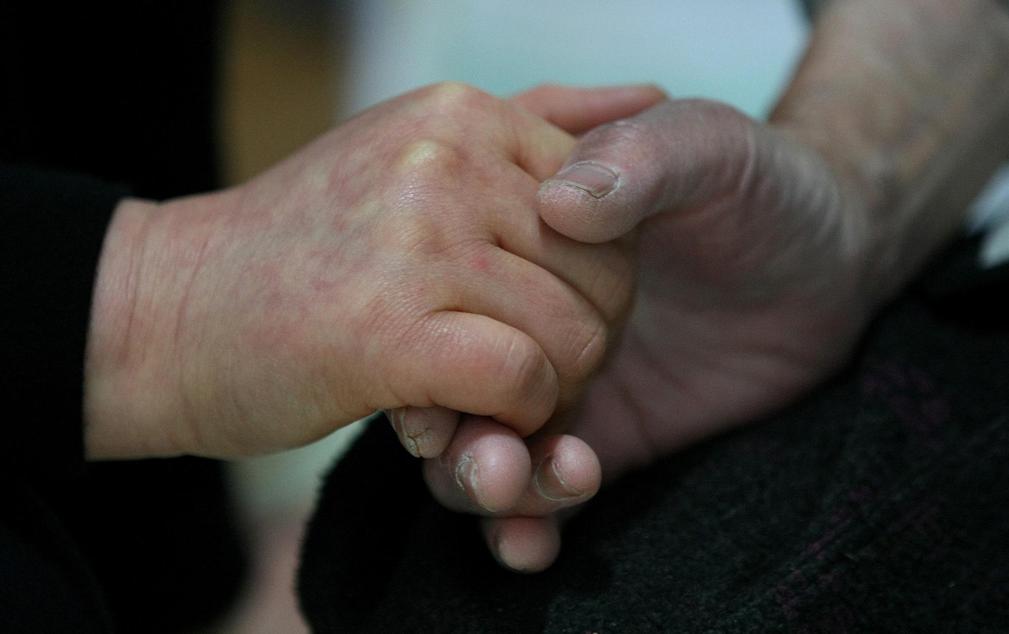 대구 주택가에서 홀로 사는 노인 집에 방문한 요양보호사가 손을 꼭 잡아주고 있다.  [중앙포토]