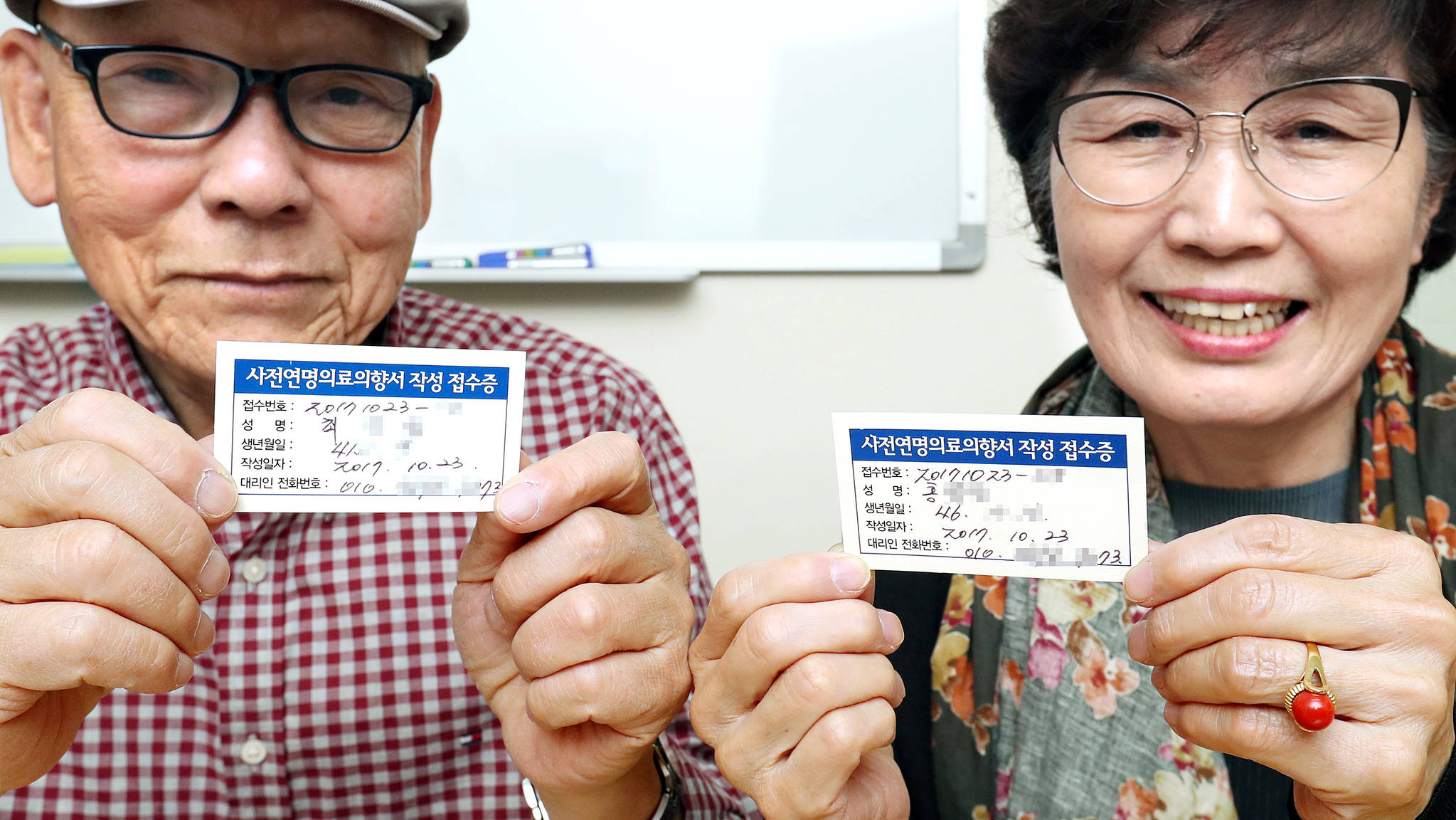 지난해 10월 연명의료결정법 시범사업 때 서울 중구국립중앙의료원에서 한 부부가 사전연명의료의향서를 작성해서 등록한 뒤 접수증을 확인하고 잇다.[중앙포토]