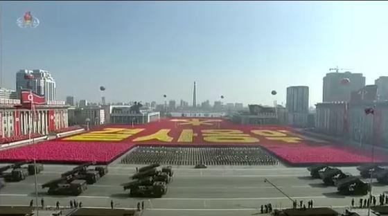 지난 8일 김일성광장에서 열린 열병식 군중대회에서 여러 가지 색깔의 꽃다발로 노동당 마크 등의 거대한 선전문구를 만들어내는 평양시민들 [사진 조선중앙TV캡처]