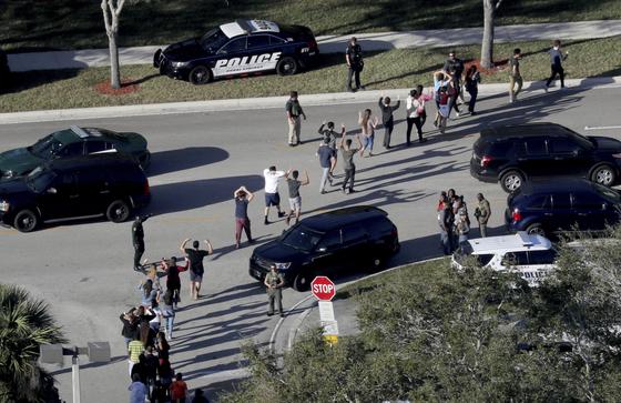 14일(현지시각) 미국 플로리다주 파크랜드에 위치한 고등학교에서 총기 난사 사건이 발생해 최소 16명이 사망했다. 학생들이 경찰을 따라 손을 들고 피신하고 있다. [AP=연합뉴스]