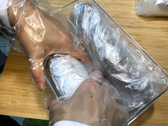 굴비 네 마리를 비닐 한장으로 만 굴비 두루마리를 밀폐용기에 차곡차곡 넣는다.