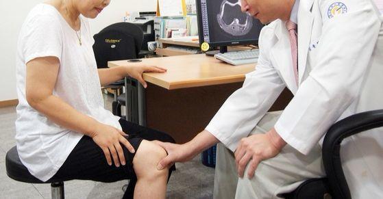 퇴행성관절염이 의심되는 환자의 무릎을 촉진하고 있다(내용과 연관없는 사진). [중앙포토]