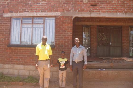 아프리카 짐바브웨 수도 하라레시에 사는 초등학생 마이클군(가운데)과 하라레시 직원 크리스씨(오른쪽). 하라레시와 국제 우호협력을 맺고 있는 천안시청 공무원들은 매달 마이클군의 학비와 생활비를 후원하기로 했다. [사진 천안시]