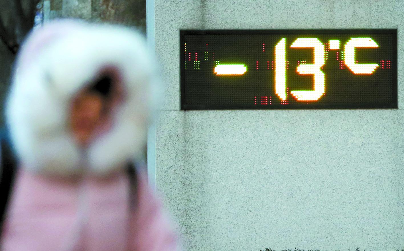 영하의 기온을 가리키는 전광판 앞으로 두꺼운 옷을 입은 시민이 지나고 있다. [연합뉴스]
