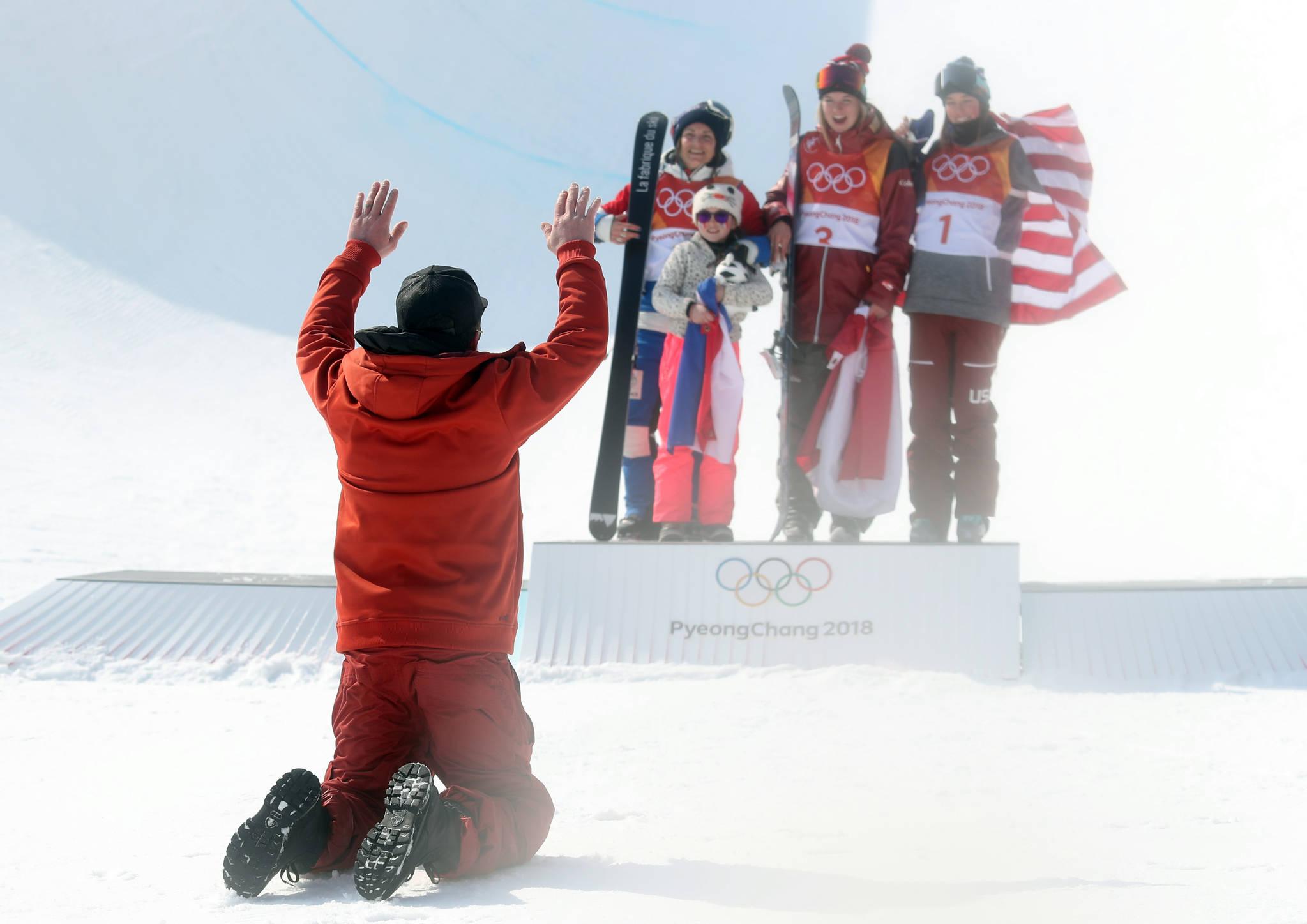 20일 강원 평창 휘닉스 스노 경기장에서 열린 2018 평창동계올림픽 여자 스키 하프파이프 결승에서 금메달을 딴 캐나다의 캐시 샤페(가운데), 은메달을 딴 프랑스의 마리 마르티노(왼쪽), 동메달을 딴 미국의 브리타 시고니가 시상대에서 활짝 웃는 동안 마리 마리노의 남편이 절을 하고 있다. 마리 마르티노 오른쪽은 딸이다.